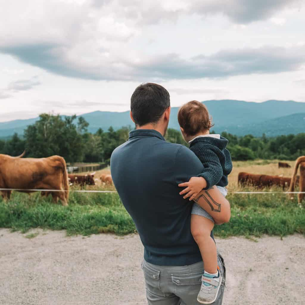 father and son looking at cows in Vemront