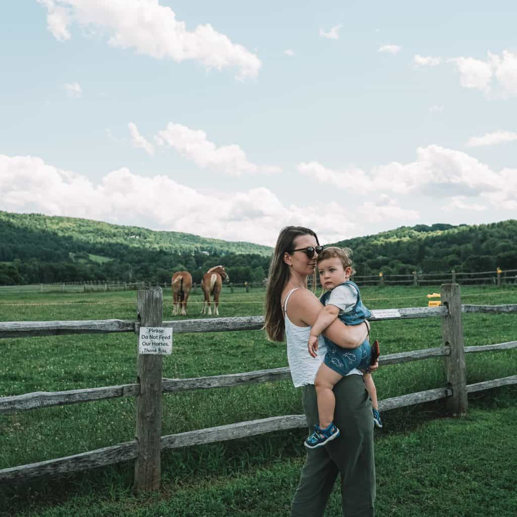 Mom holding a baby at the farm in vermont