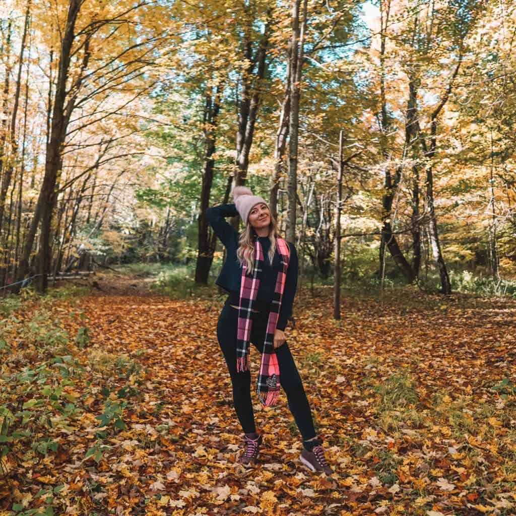 Girl posing inside the hiking trail covered with colorful leaves