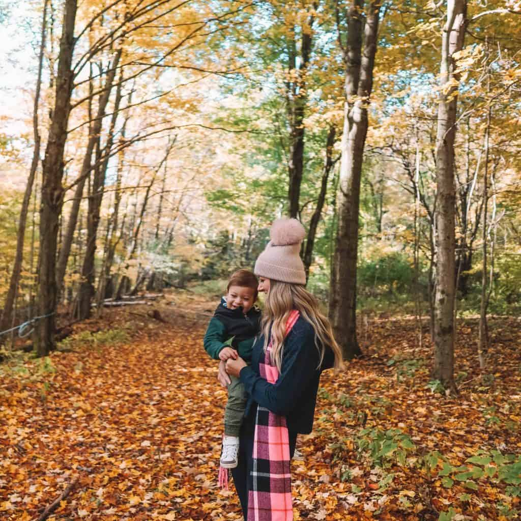Mom and child standing in the middle of fall foliage in Catskills