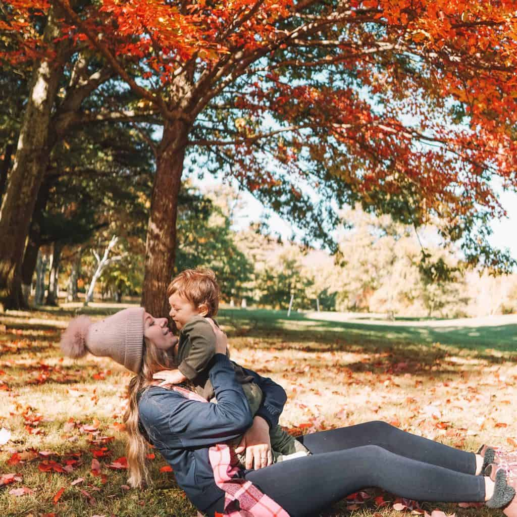 Mom and baby hugging under the colorful tree in Catskills