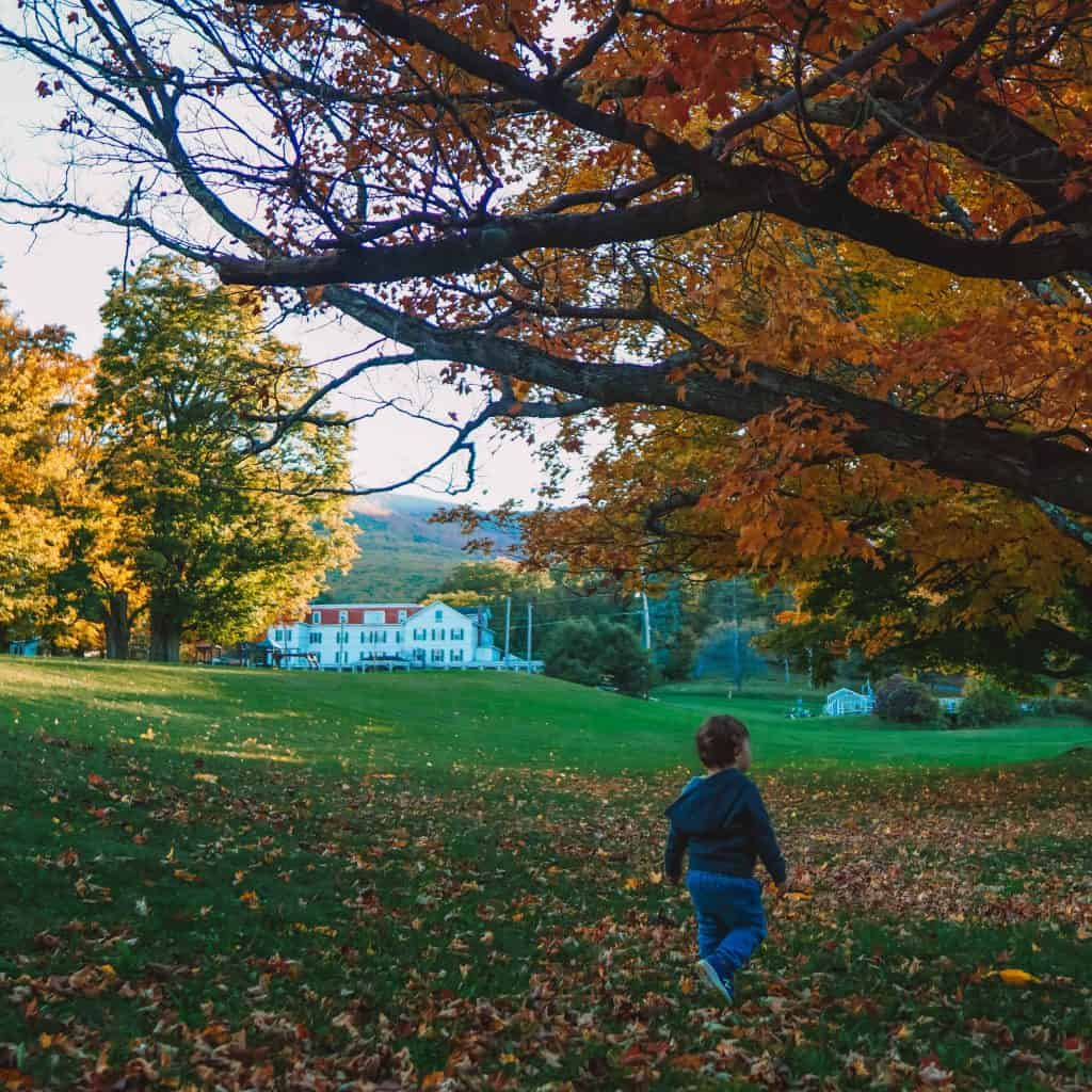 Baby walking in front of Winter Clove Inn during fall foliage in Catskills