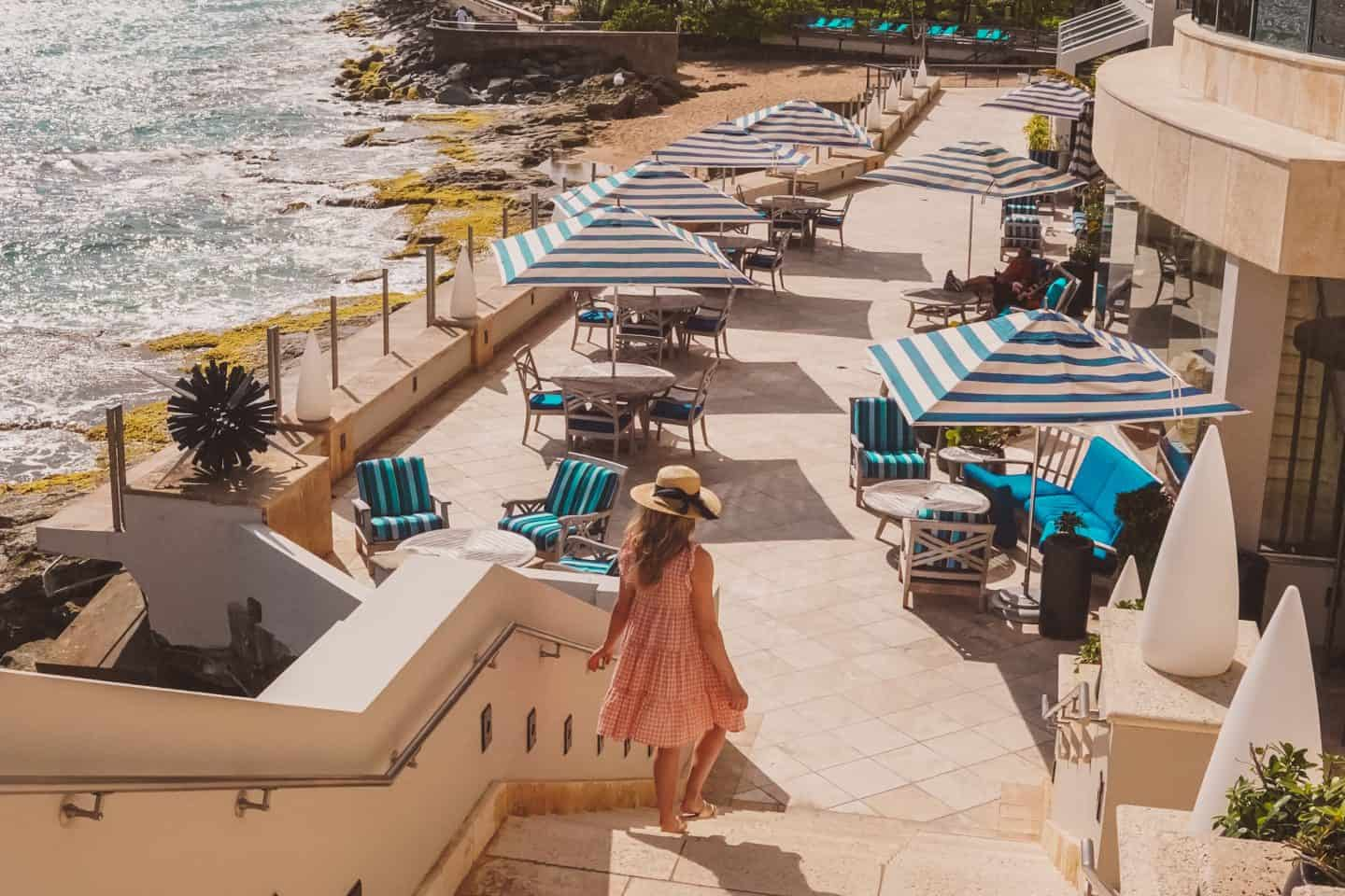 girl walking down the bach resort in dress and a sun hat. Another idea for beach vacation packing