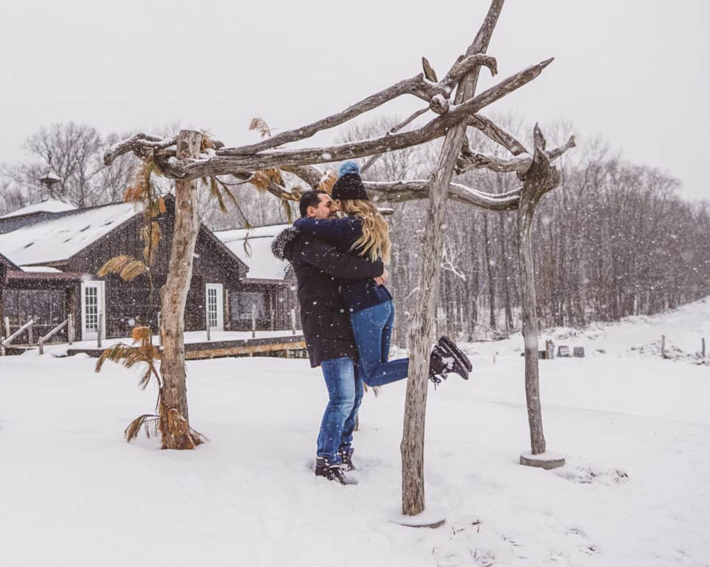 Couple hugging in a snow at Benmarl Winery