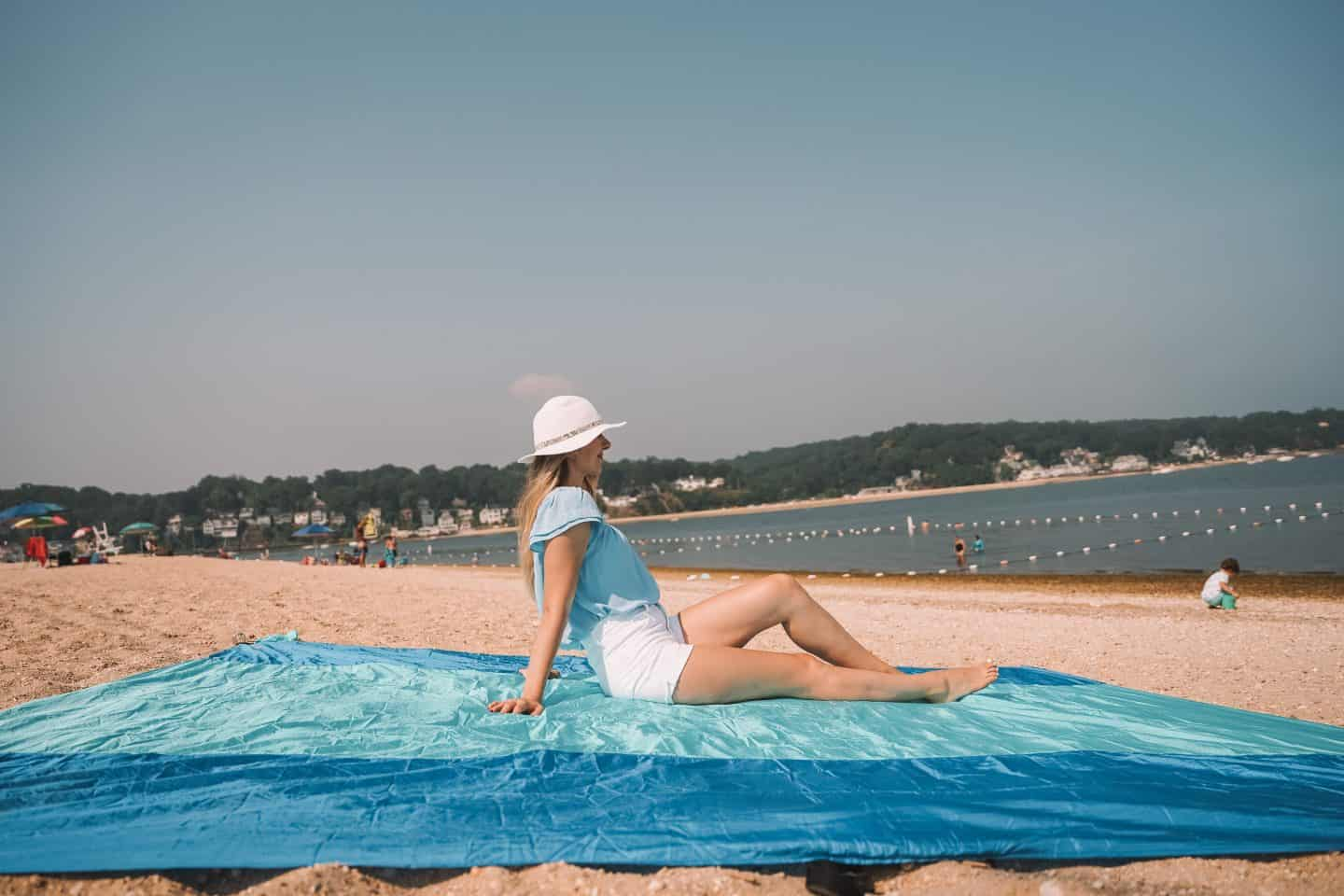 beach packing list: Sand free blanket. Girl relaxing on it while at the beach