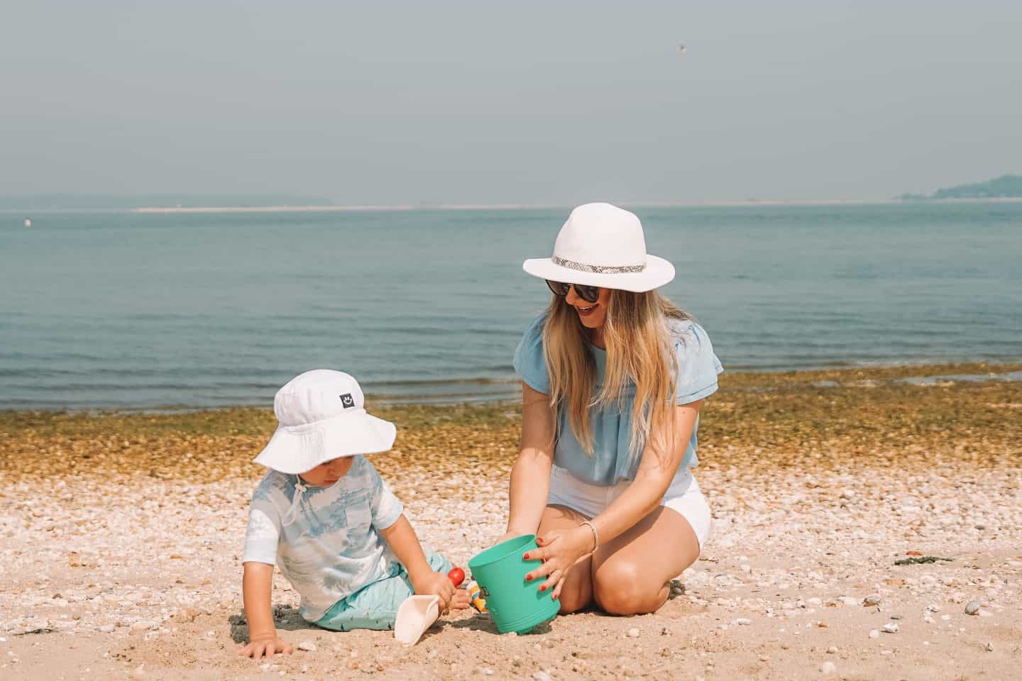 mom and son playing on the beach with beach toys.