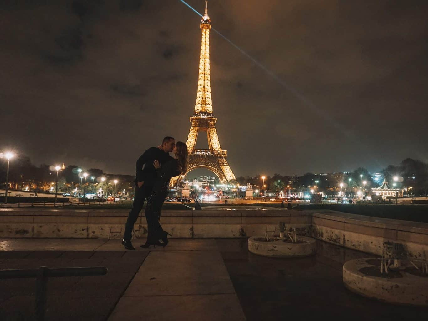 couple kissing at night in front of sparkling Eiffel Tower