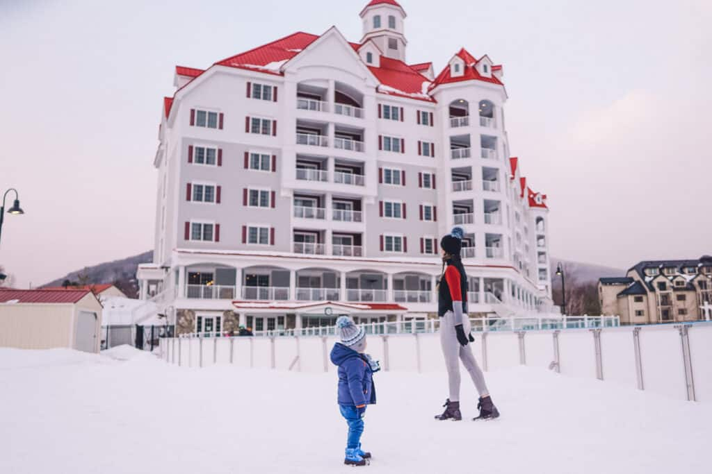 mom and son standing in front of a family friendly resort near ice Castles Lincoln, NH.