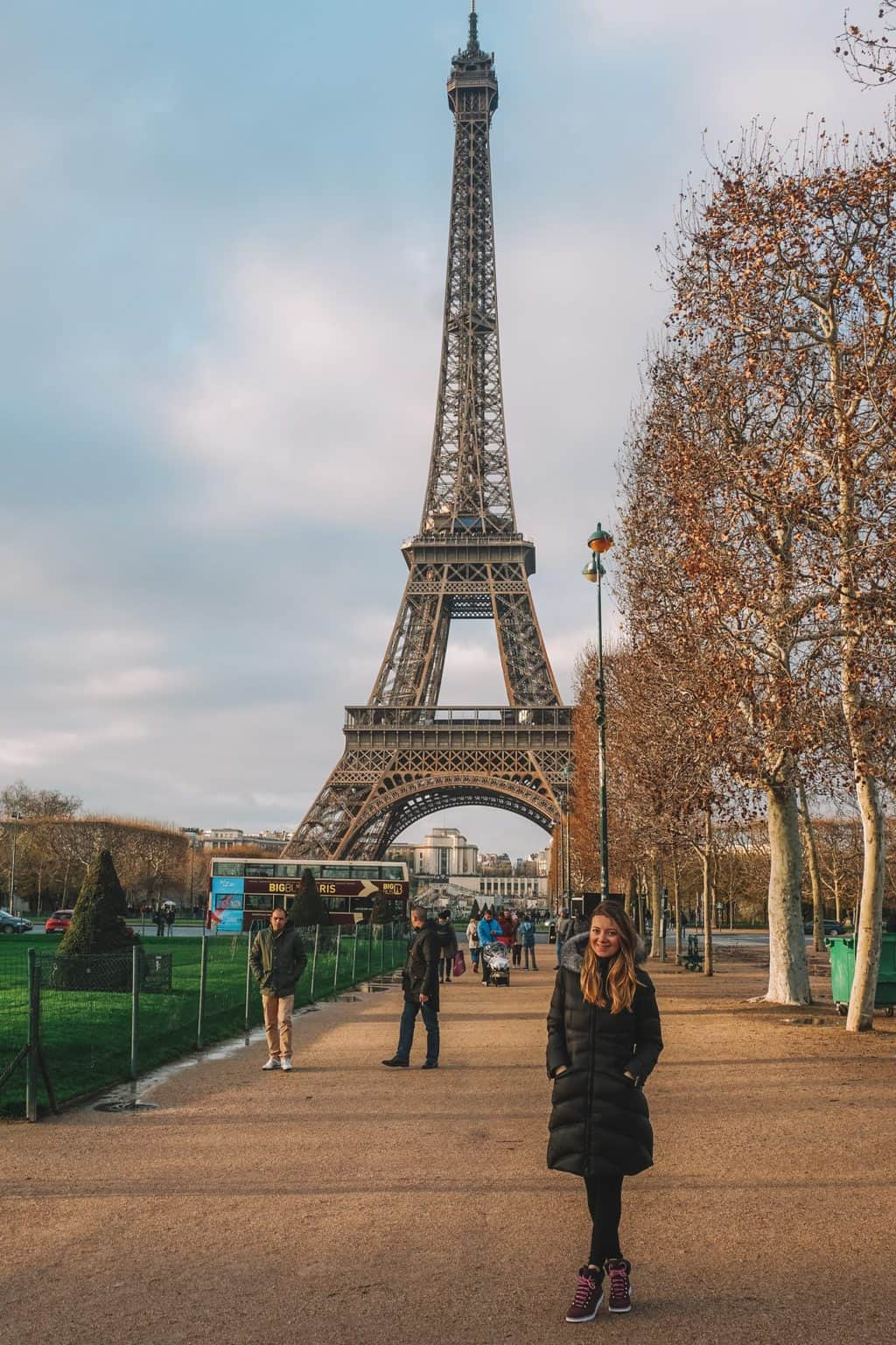 Girl happily posing in front of the Eiffel Tower Paris