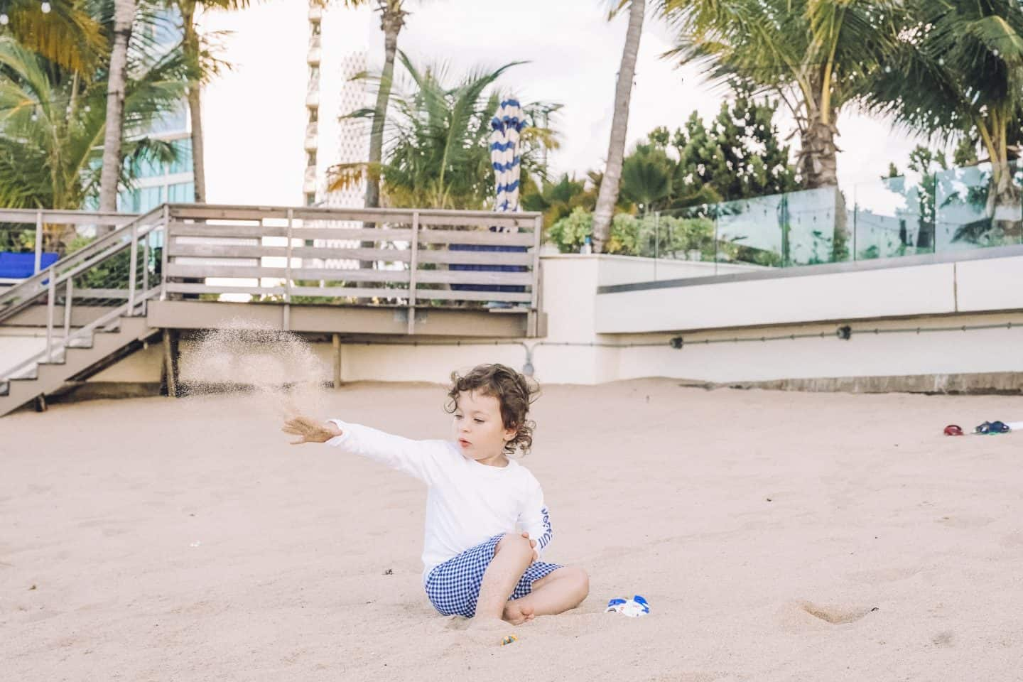 Toddler in his rash guard and a swim trunk playing in the sand. Another must have item in your beach vacation packing list