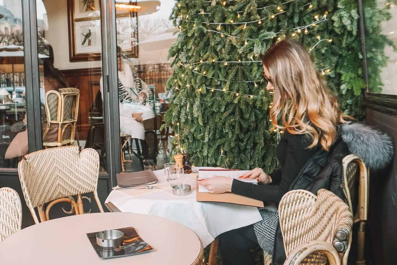 Girl looking at the menu in Paris Cafe
