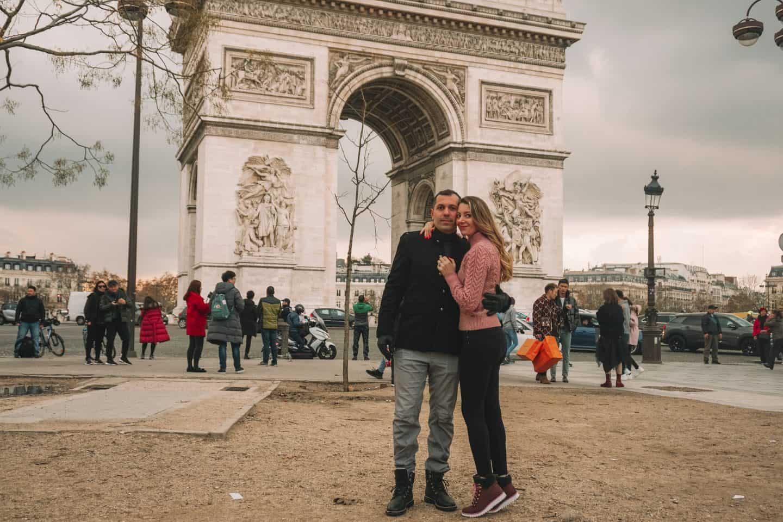 Couple hugging in front of the Arc De Triumphe Paris